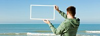 Gulls flying above sea framed in picture frame held aloft by man on beach