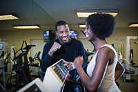 Personal trainer motivating woman on treadmill