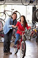 Mixed race father helping daughter choose bicycle in shop