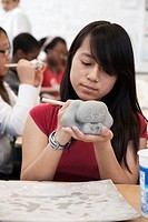 Pacific Islander student working with clay in classroom