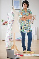 Hispanic woman standing with dressmakerÕs dummy