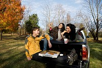 Friends eating pizza in back of truck