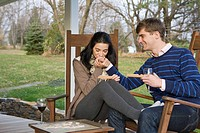 Caucasian couple playing scrabble on porch