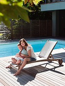 Boy and mother on chair by pool