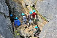 School children during survival day clambering on eroded rocks of ravine in the nature reserve Fondry des Chiens, a sinkhole near Nismes at Viroinval ...