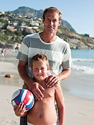 Father and son on beach with ball
