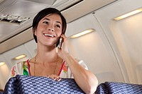 Young woman using cellphone on airplane