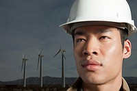 Man in hard hat by wind turbines