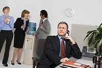 Businessman on telephone with people gossiping by water cooler