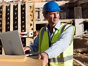 Mature man uusing laptop on construction site