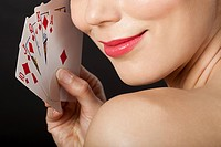 Young blonde woman playing cards