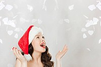 Young brunette woman wearing Santa hat with confetti