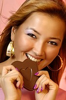 Beautiful young woman eating a heart-shaped chocolate candy Valentines Day concept in bright pink colors