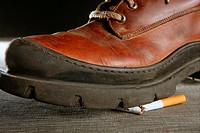 broken cigarette tread by a boot, tobacco addiction metaphor