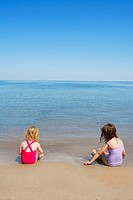 tow sisters sit on beach bathing suit swimsuit back view summer vacation