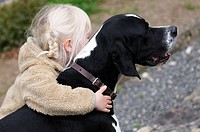 4 year old child hugging her pet dog