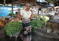 A woman wearing traditional ikat dress carries vegetables on a pannier at a market in Sumba Indonesia