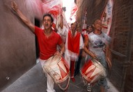 The Giraffe Contrada celebrate winning the Palio with a street procession through the streets, Siena, Italy