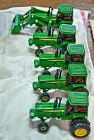 This vertical image shows a row of 5 green John Deere vintage toy tractors being prepped for an antique show, freshly washed and drying on a towel Foc...
