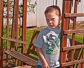This Caucasian 5 year old boy is sad and upset as he's leaning against a cedar swing outside His eyes and facial expression and body language convey d...