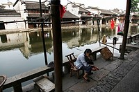 Elderly woman sitting beside the river, Nanxun, Huzhou, Zhejiang Province, China