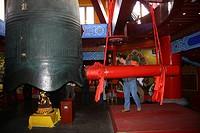 Man strike a large bronze bell, Tianning Pagoda, Tianning Temple, Changzhou, Jiangsu Province, China