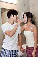 young couple brushing teeth together