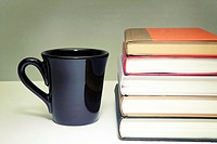 pile of books and cup