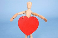 heart shape hung on the wooden doll