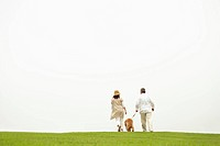 Mature husband and wife walking their dog in a park