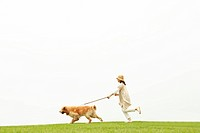 Mature woman running with her dog in a park