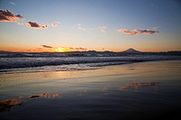 Beach at sunset, with Mt Fuji in silhouette in the background. Fujisawa, Kanagawa Prefecture, Japan