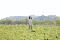 Portrait of young woman standing in field, Kyoto prefecture, Japan
