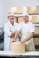 Portrait of smiling cheese makers binding new farmhouse cheddar cheese wheel with cheesecloth