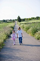 A boy and a girl hand in hand walking on a country road