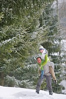 Couple piggybacking in snowy woods