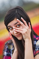 a girl with her hand over her face and peeking through her fingers