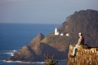 oregon, united states of america, a man sitting on a cliff looking out over the pacific ocean with heceta head lighthouse in the background