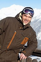 Young man in ski wear smiling at camera