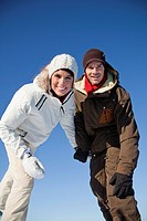 Young couple wearing ski wear, smiling at camera