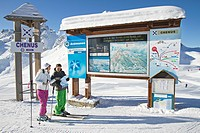 Couple of skiers looking at map, Courchevel, France