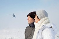 Young couple in winter clothes, helicopter in background