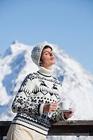 Young woman with coffee cup, enjoying winter sun, mountains in background (thumbnail)