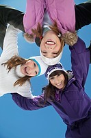 Three teenage girls in ski clothes, smiling at camera