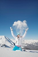 Girl in ski clothes, throwing snow in air