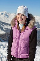 Teenage girl in ski clothes, smiling at camera