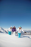 Three teenage girls in ski clothes, walking in snow