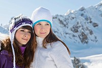 Two teenage girls in winter clothes, embracing