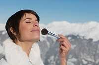 Young woman applying make_up, mountains in background
