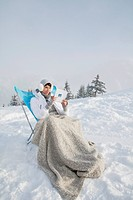 Young woman reading in snow